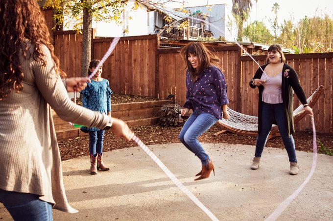 family playing jump rope outside