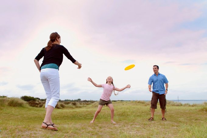 family throwing a frisbee outside