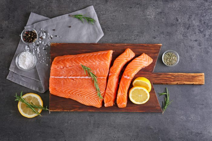 Cutting board with fresh salmon fillet and lemons on table