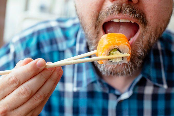 close up of man eating sushi