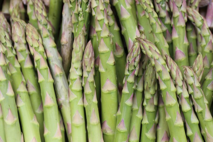 Close up outdoor view of asparagus tips rows. Picture taken in a french market during spring. Pattern of green, yellow and purple thin vegetable elements. Abstract natural image. Rough texture.