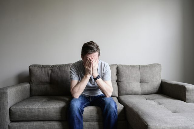 man sitting on couch at home with head in hands