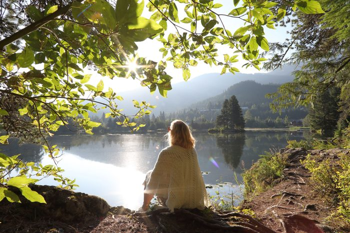 woman sitting near lake looking off into distance
