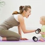 woman on yoga mat holding weights and playing with baby