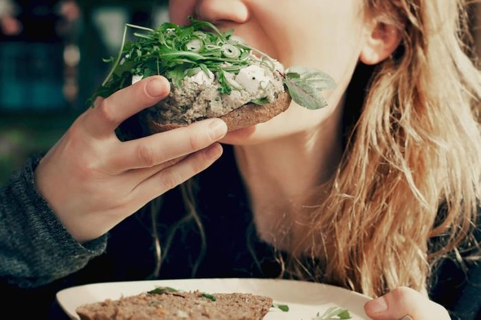 woman taking a bite out of a vegetable sandwich