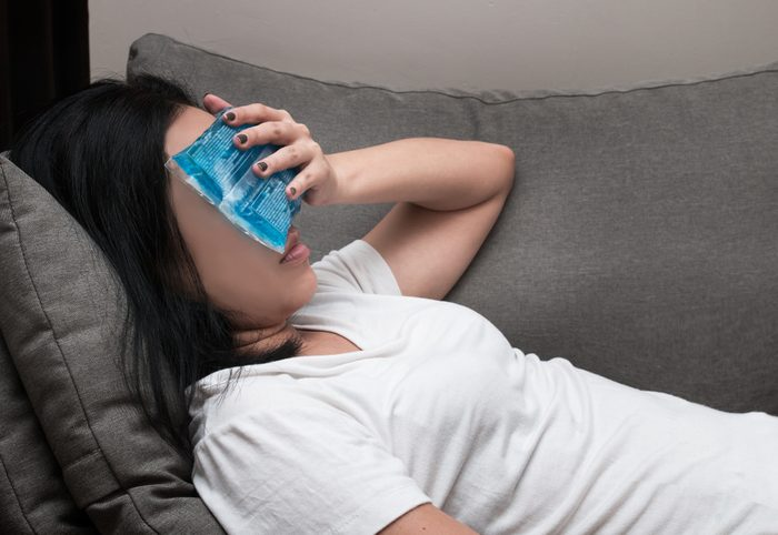 Asian woman with ice cold pack on her forehead for relief fever headaches and migraines