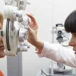 eye doctor checking woman's vision with machine