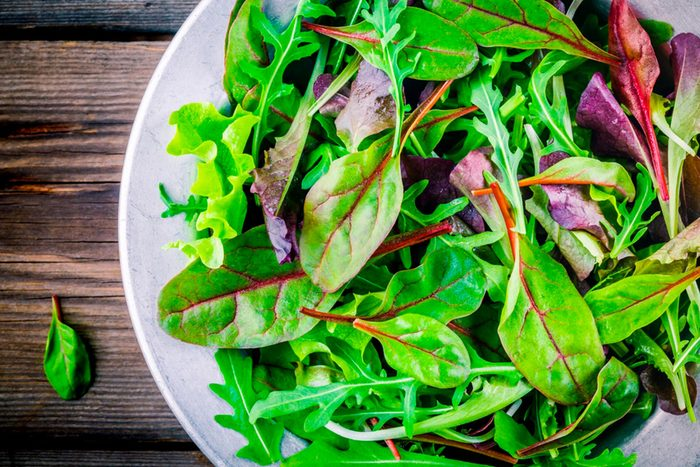 Leafy greens in a white bowl on a wood background