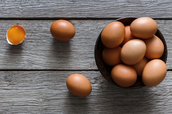 Fresh chicken brown and white home eggs with cracked eggshell and yolk in bowl at rustic wood table. Top view with copy space. Rural still life, natural healthy food and organic farming concept.