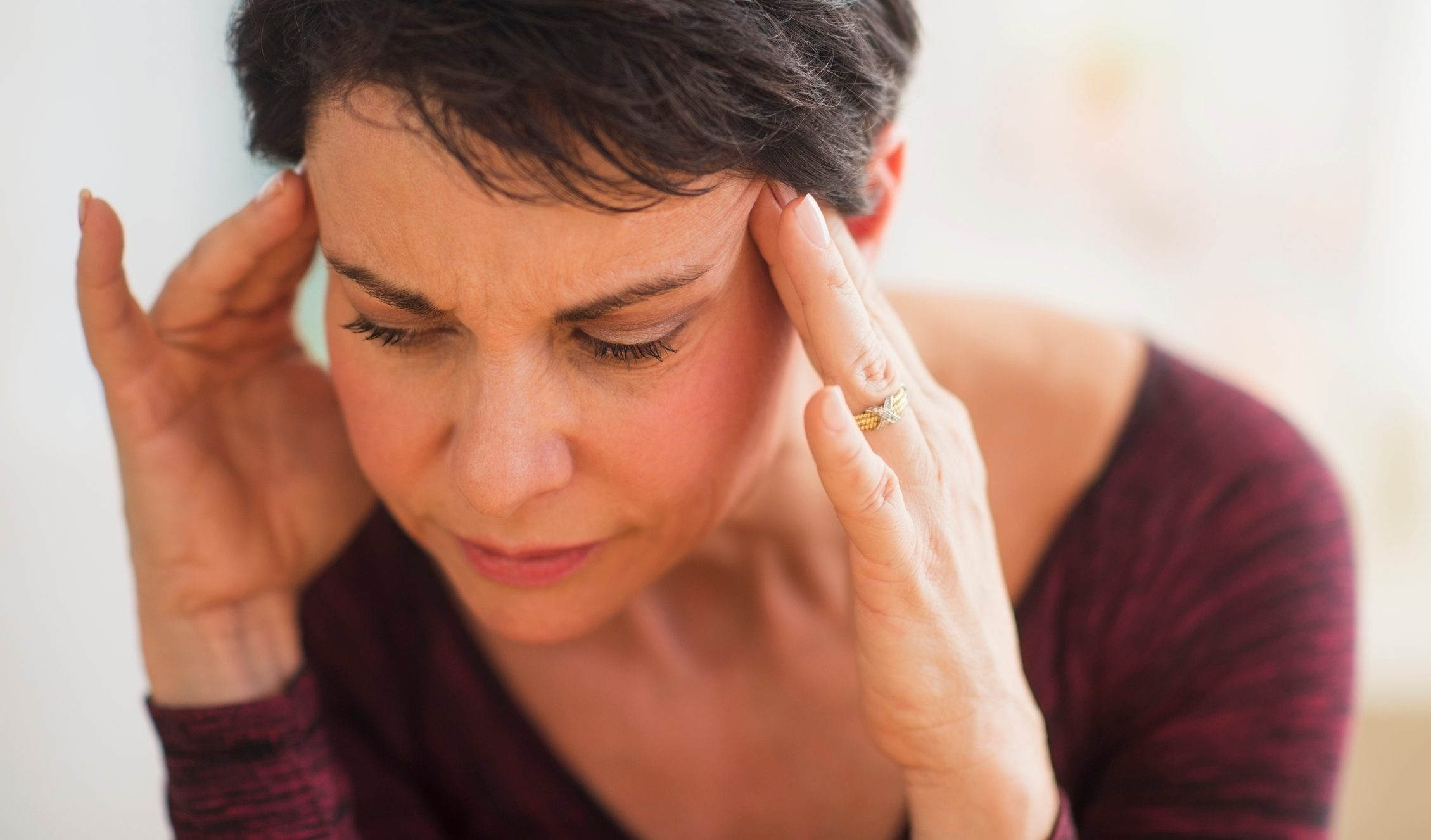 close up of woman with hands on forehead stressed trying to remember