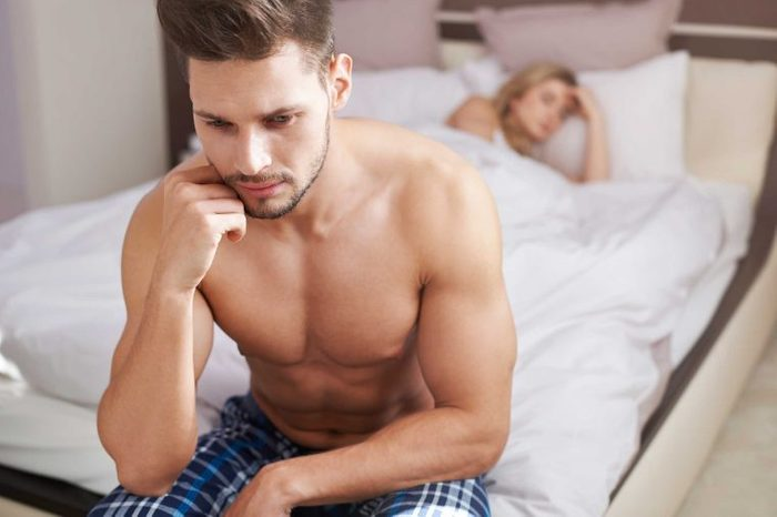 Man turned away from woman in bed