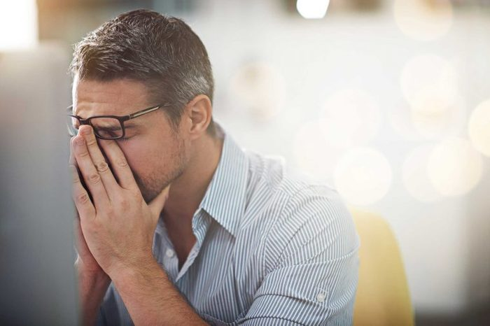 Stressed man putting his hands to his face