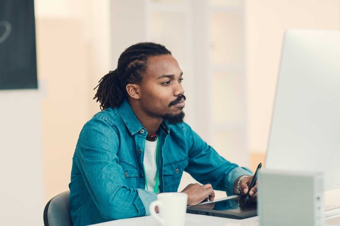 young black man with beard sitting at computer