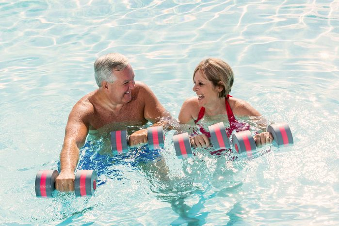 mature man and woman exercising in pool
