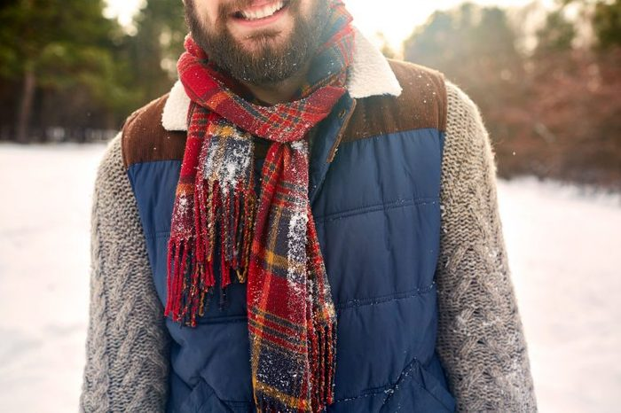 Bearded man in a scarf and winter vest in the snow.