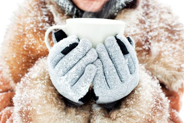 Woman in a fur trimmed collar and gloves holding a mug.