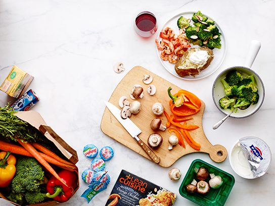a kitchen counter with a cutting board and loads of veggies