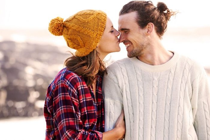 outdoorsy woman kissing man on the nose
