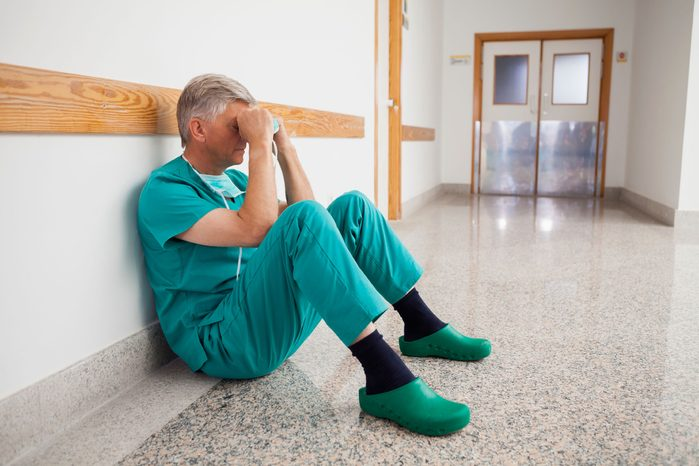 Gray-haired doctor sitting on the floor of a hospital hallway