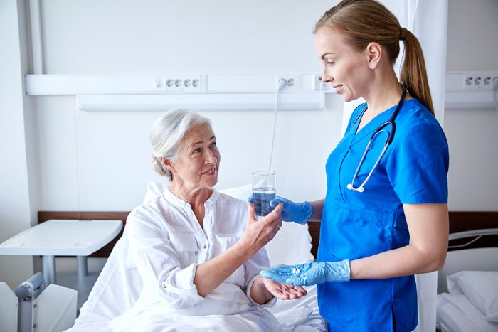 young female nurse handing an elderly patient pills and water