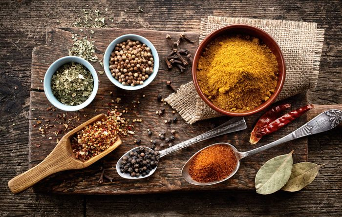 variety of spices on worn wooden cutting board