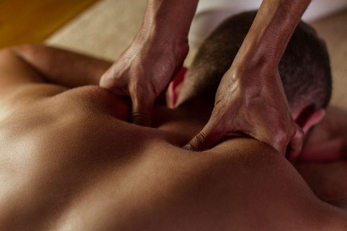 close-up of hands massaging a man's upper back