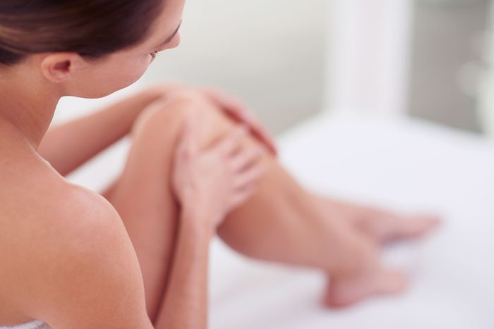 woman in towel touching her knees