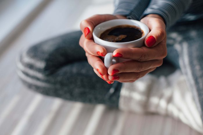 woman's hands cupping a mug of coffee