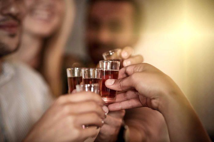 closeup of hands holding shot glasses