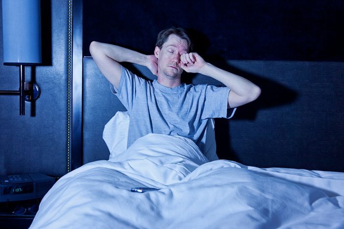 man sitting up in bed, waking up and rubbing one eye