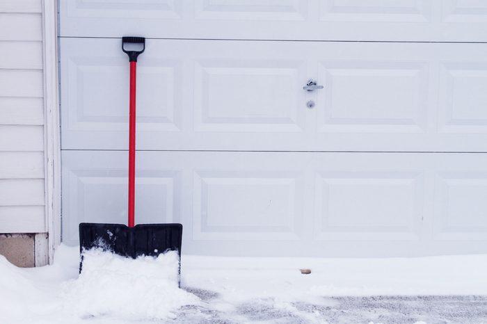 snow shovel leaning against garage door
