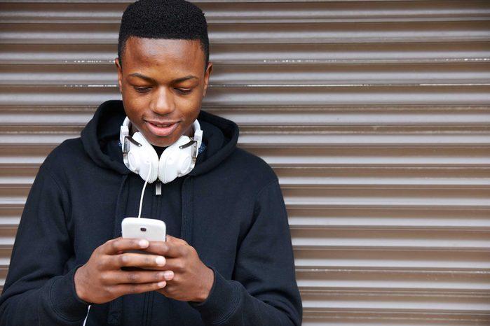 man texting on smartphone, headphones around neck