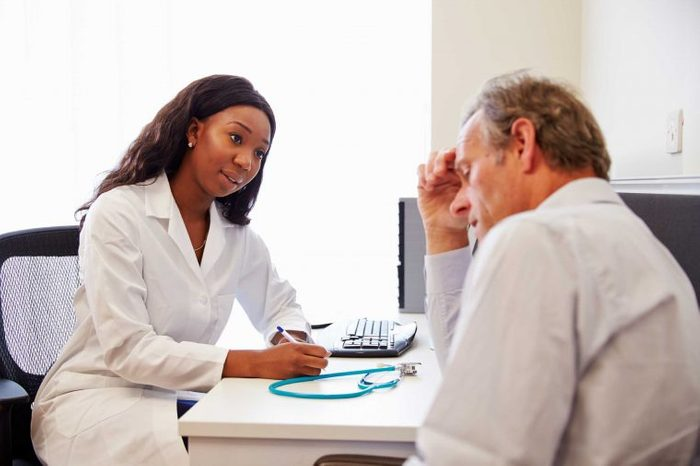 Woman doctor talking to a male patient at the doctor's office.