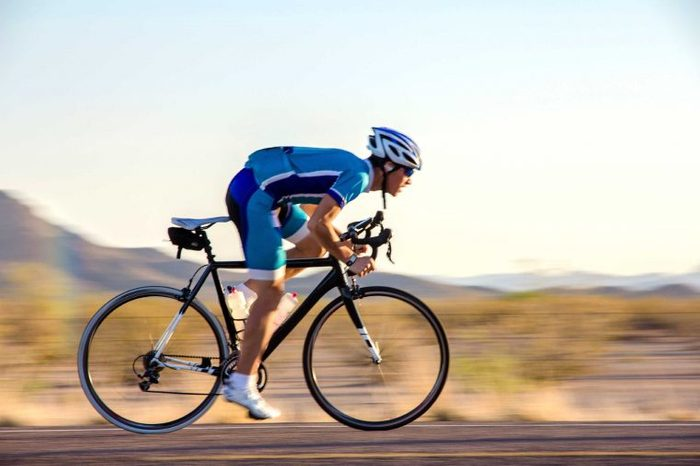 Elite athlete cyclist biking on a road.