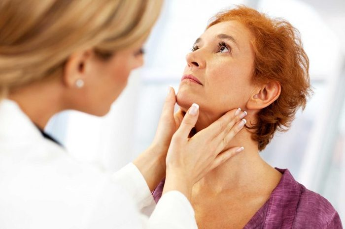 Doctor checking a woman patient's tonsils.