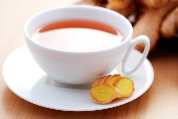 white cup of tea with ginger on side