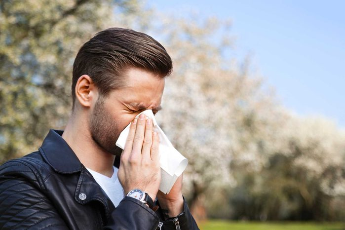 man blowing his nose outside