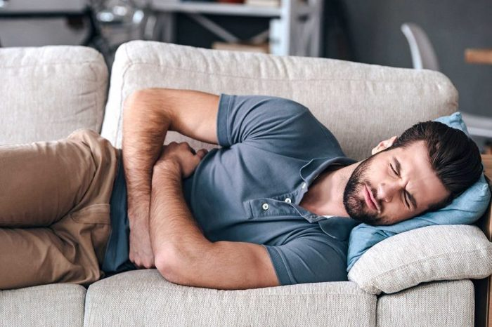 Man lying on his side on the couch with stomach pain.