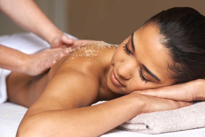hands applying a scrub on woman's back during massage