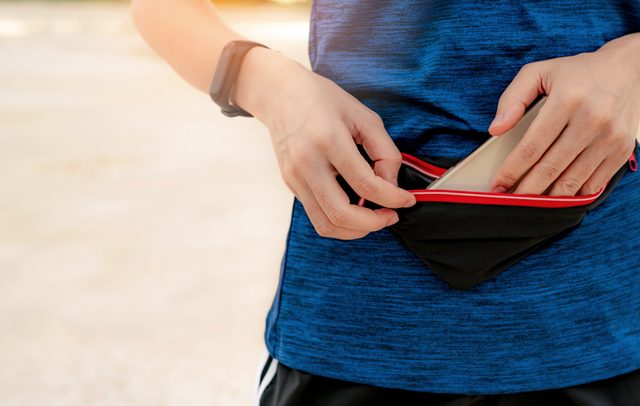 woman putting phone into fanny pack