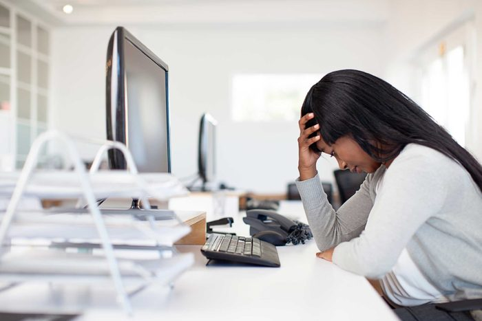 woman sitting at desk with head in hand