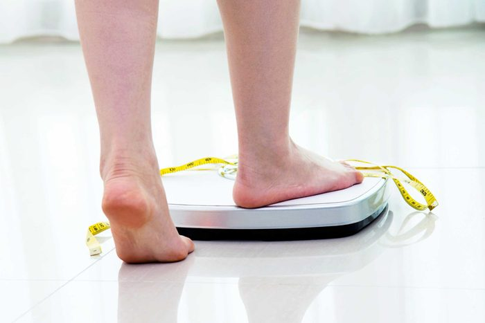 woman stepping scale with measuring tape