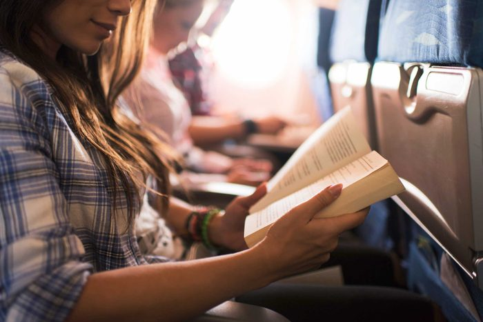 woman on a plane reading a book