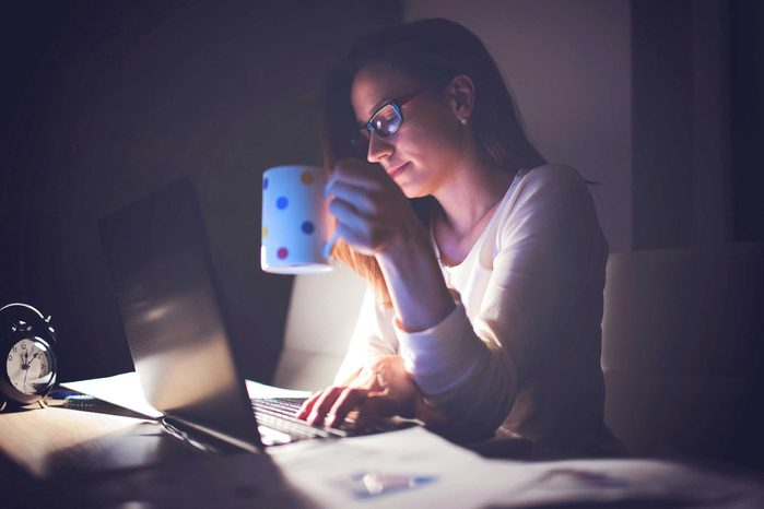 woman holding a cup of coffee and working at a computer in a dark room