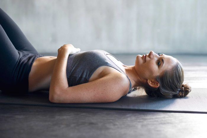 woman in workout gear reclining on a yoga mat