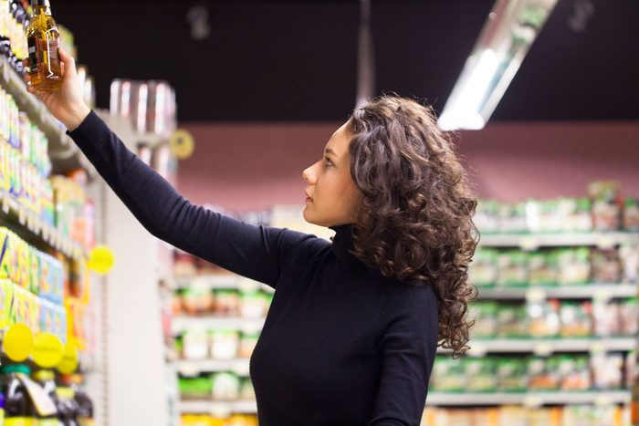 woman looking at label in supermarket