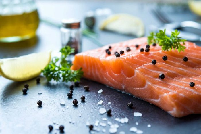Salmon filet with parsley and capers, with a lemon wedge next to it.