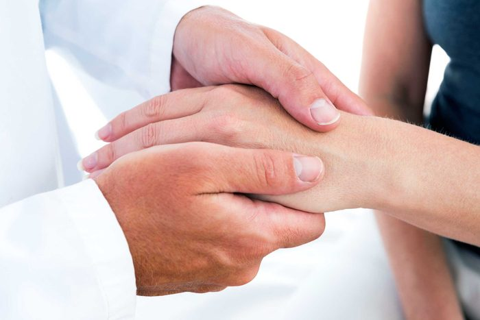 doctor's hands holding a patient's hand