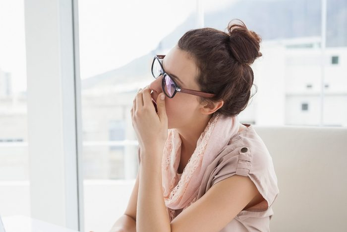 Woman with glasses yawning into her hand