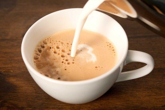 milk pouring into a mug of coffee